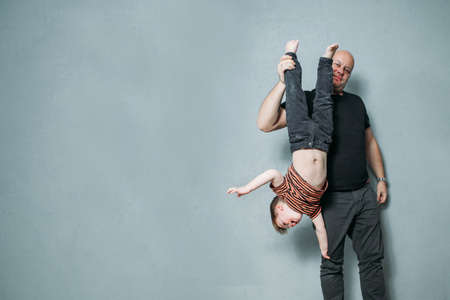 funny young dad keeps his sons legs upside down Stock Photo