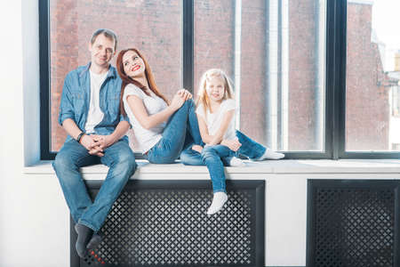 apartment: Happy family mother father child portrait sitting on window sill