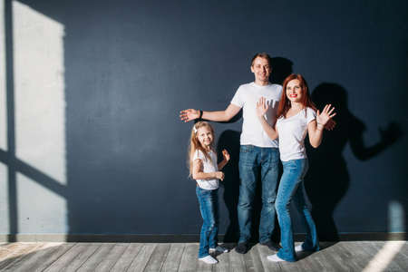 Happy family portrait standing on gray background wooden floor room window sunny day