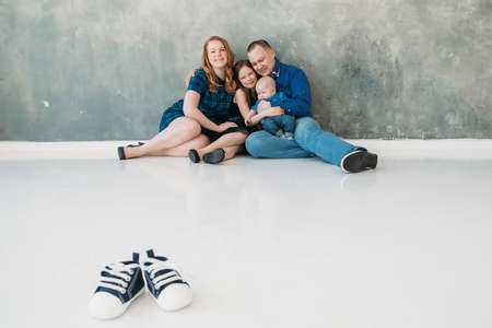 Happy family portrait siting on gray background white floor room sunny day