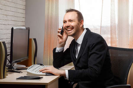 A young male manager works at a computer in the office. A black cat on the table makes it difficult to work. Telework. The manager looks in surprise at the black cat and smiles.
