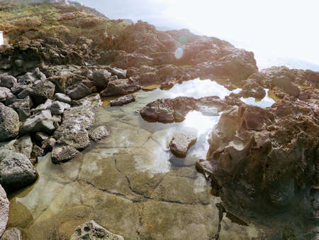 Shore is an island of volcanic lava and stones in the ocean Фото со стока