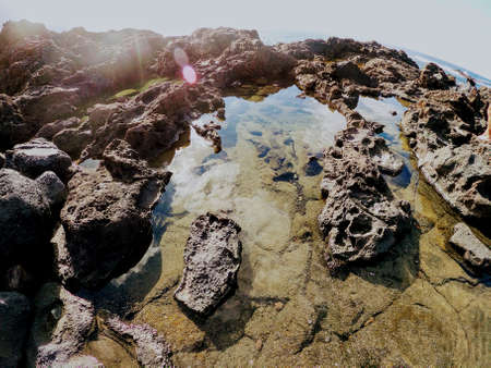 Shore is an island of volcanic lava and stones in the ocean. Transparent puddle with sea water.