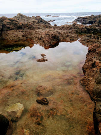 Volcanic peninsula of stones. Large puddles of sea water with reflections.