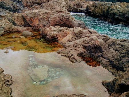 Volcanic peninsula of stones. Large puddles of sea water with reflections. Green algae.