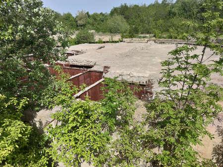 Old soviet rusty bomb shelter. Around concrete blocks. Green trees and plants. Olishkany - Moldova