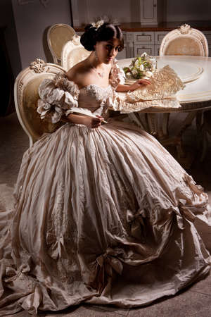 attractiveness: Young beautiful woman in a wedding dress sitting at the round table