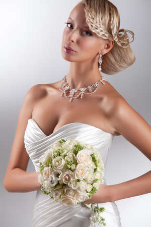 Young beautiful blonde woman in a wedding dress on a studio background Stock fotó