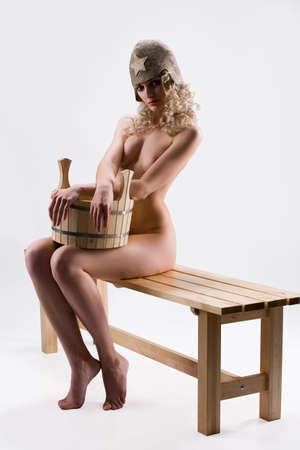 Junge blonde nackte Frau auf einer Holzbank mit einem Holzzuber