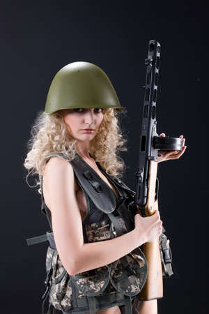 Young blonde woman dressed in military style with weapon