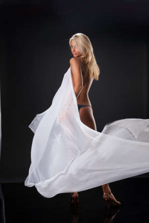 sex appeal: Young topless blonde woman with a waving white fabric on black reflecting background Stock Photo