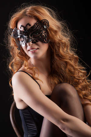 red haired woman: Young red- haired woman in a black lingerie on a studio background