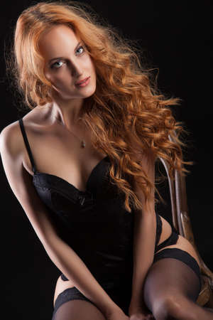 haired: Young beautiful red- haired woman in a black lingerie sitting on an old Viennese chair Stock Photo