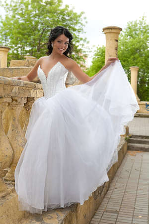 diferent: Young dark-haired beautiful woman in a wedding dress in diferent outdoor situations