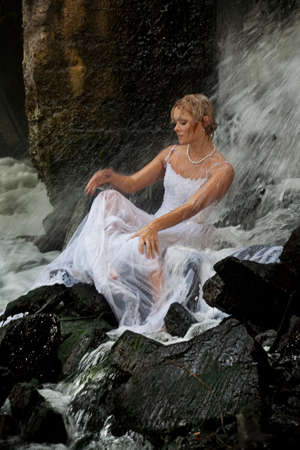 attractiveness: Young blonde woman in a white wedding dress near the waterfall