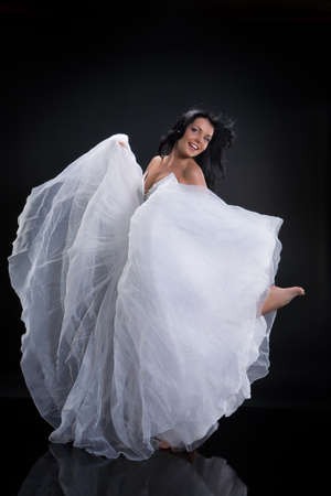 barefooted: Young beautiful woman in a wedding dress on a studio background