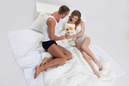 home accessories: Young beautiful woman and man in lingerie with toys and home accessories