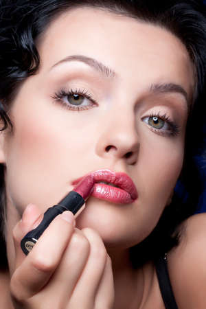 sex appeal: Young beautiful woman applying cosmetics onto her face Stock Photo