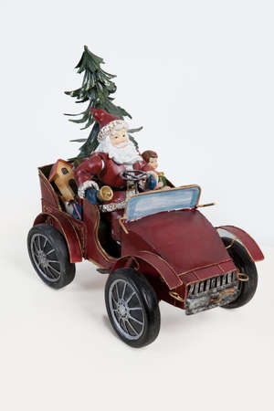 klaus: Statuette of Santa Klaus sitting in an old car on isolated background Stock Photo