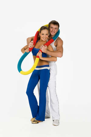 training device: Young woman and man with the training device on isolated background