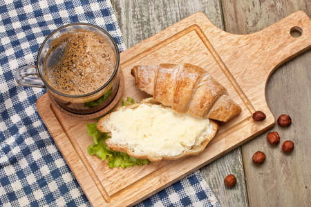 bread and butter: Bread, butter, coffee and greenery on a studio canvas background Stock Photo