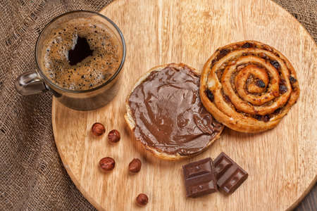 bread and butter: Cup of coffee, bread, butter and nuts on a wooden table Stock Photo