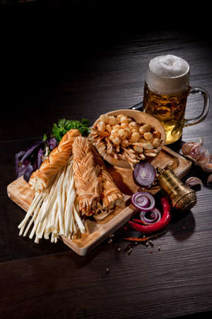 bier: Cheese, glass of bier and vegetables on a wooden table