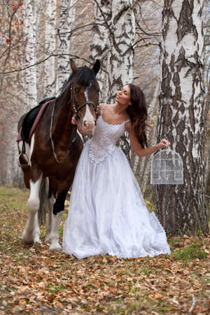 affectionate action: Young woman and horse in a forest