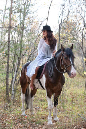 affectionate actions: Young woman and horse in a forest