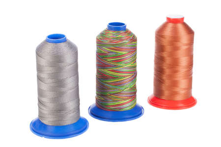 Bobbins with silk thread on an isolated studio background