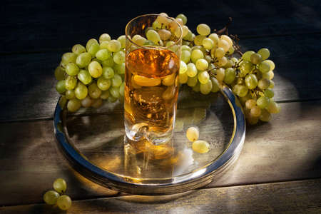 old desk: Glass of wine and grape on an old wooden desk Stock Photo