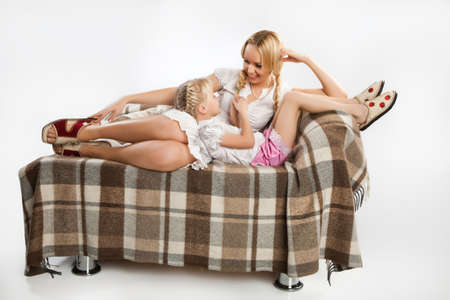 Young woman and little girl sitting on sofa and smiling