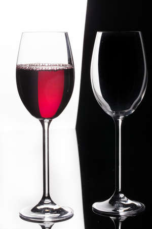 Glass with a red wine on a glass studio background Foto de archivo