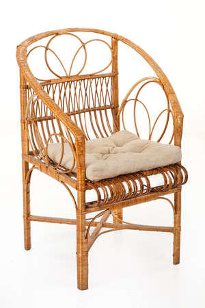 Wicker armchair with a pillow on an isolated studio background