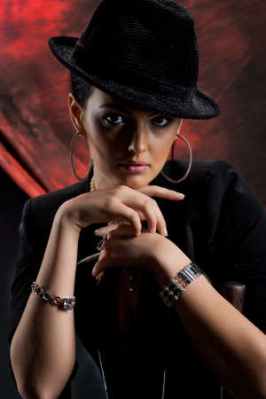 Young beautiful woman in a black clothing on a red and black studio background