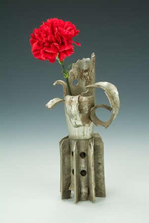 Detonated mine and carnation on a studio background
