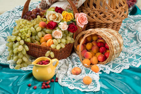 Wicker basket and different fruits on a studio background