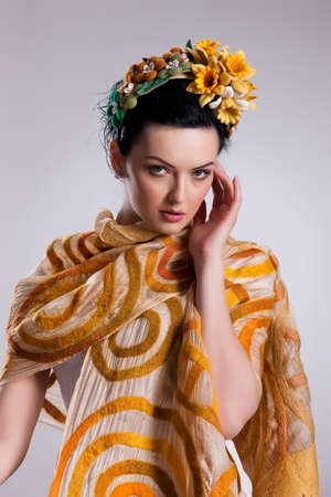 Young attractive woman dressed in fashionable handmade clothing on isolated background