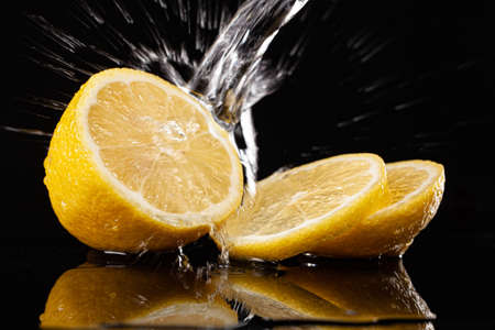 Lemon and pouring water on a black glass background Stock Photo