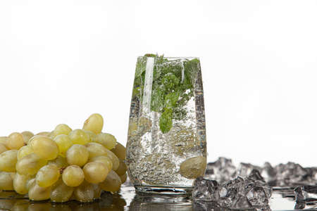 Glass of water, mint and grape on a glass background Stock Photo