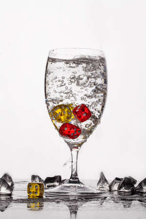 Dices, crystals of ice and glass of water on a glass background