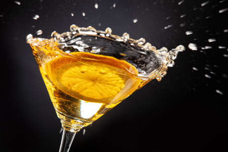 Slice of orange falling into the glass of juice Stockfoto