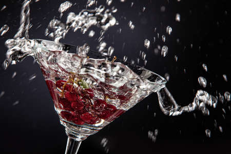 Bunch of red currant falling into the glass of water