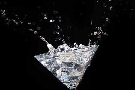 Glass with ice crystals with water splashes
