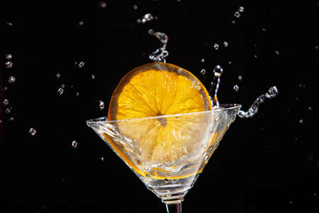 Glass with orange and ice with water splashes
