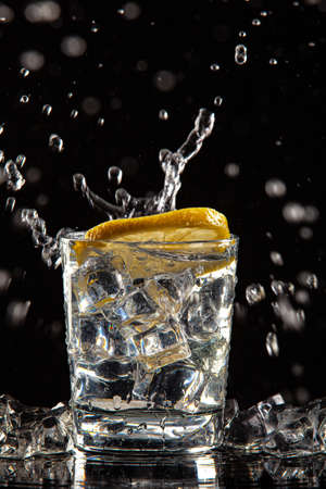 Glass of water, ice crystals and lemon on a black studio background Stockfoto