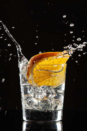 Glass of water, orange and splash of water on a black studio background