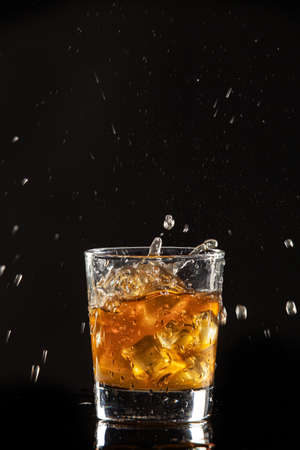 Glass of beverage, ice and lemon on a black studio background