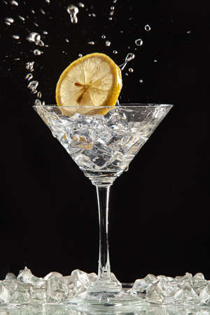 Glass of water, lemon and watersplashes on a black studio background