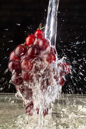 Bunch of grapes and stream of water on a studio background